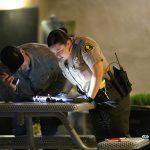 Detectives inspect rifle left behind by suspect. (Hugo Valdez, Victor Valley News)