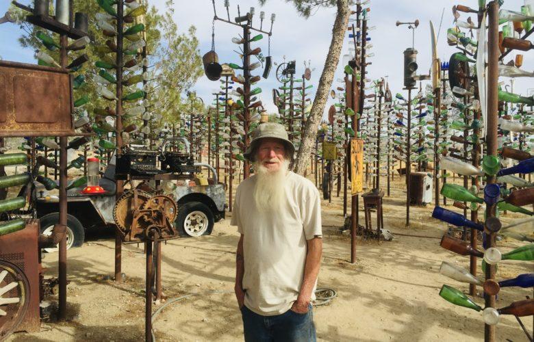 Elmer Long posing for a photo inside his world-famous bottle tree farm on May 17, 2015. (Hugo C. Valdez, Victor Valley News)