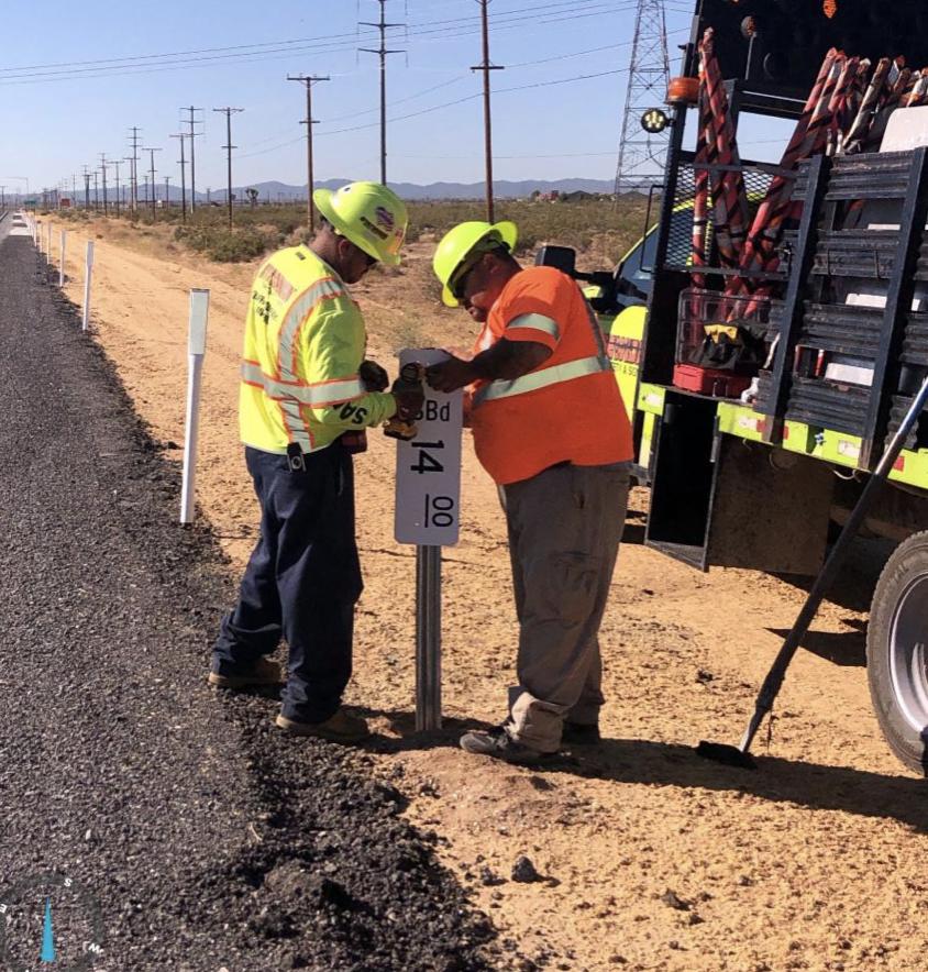 Crews installing a roadside sign/mile marker.